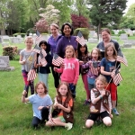 Brownie Scouts and their leaders putting out flags